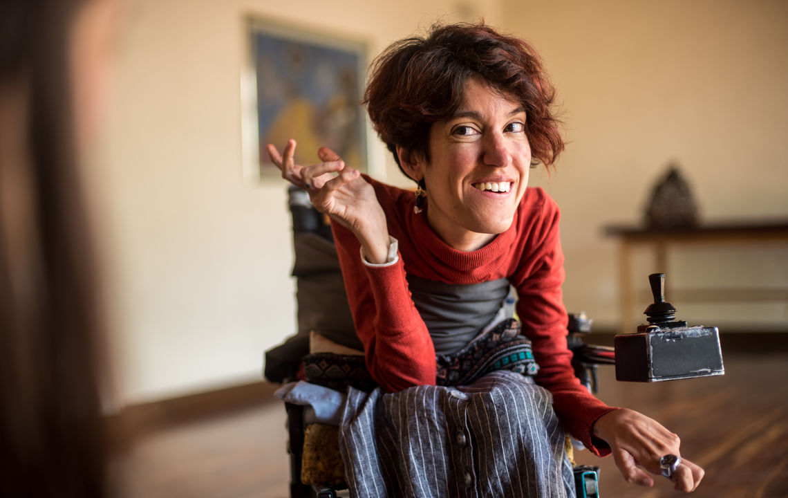 A woman in a wheelchair looks at the camera