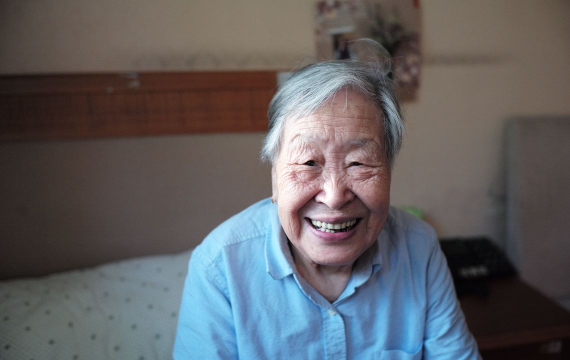 senior woman smiling and sitting on bed.