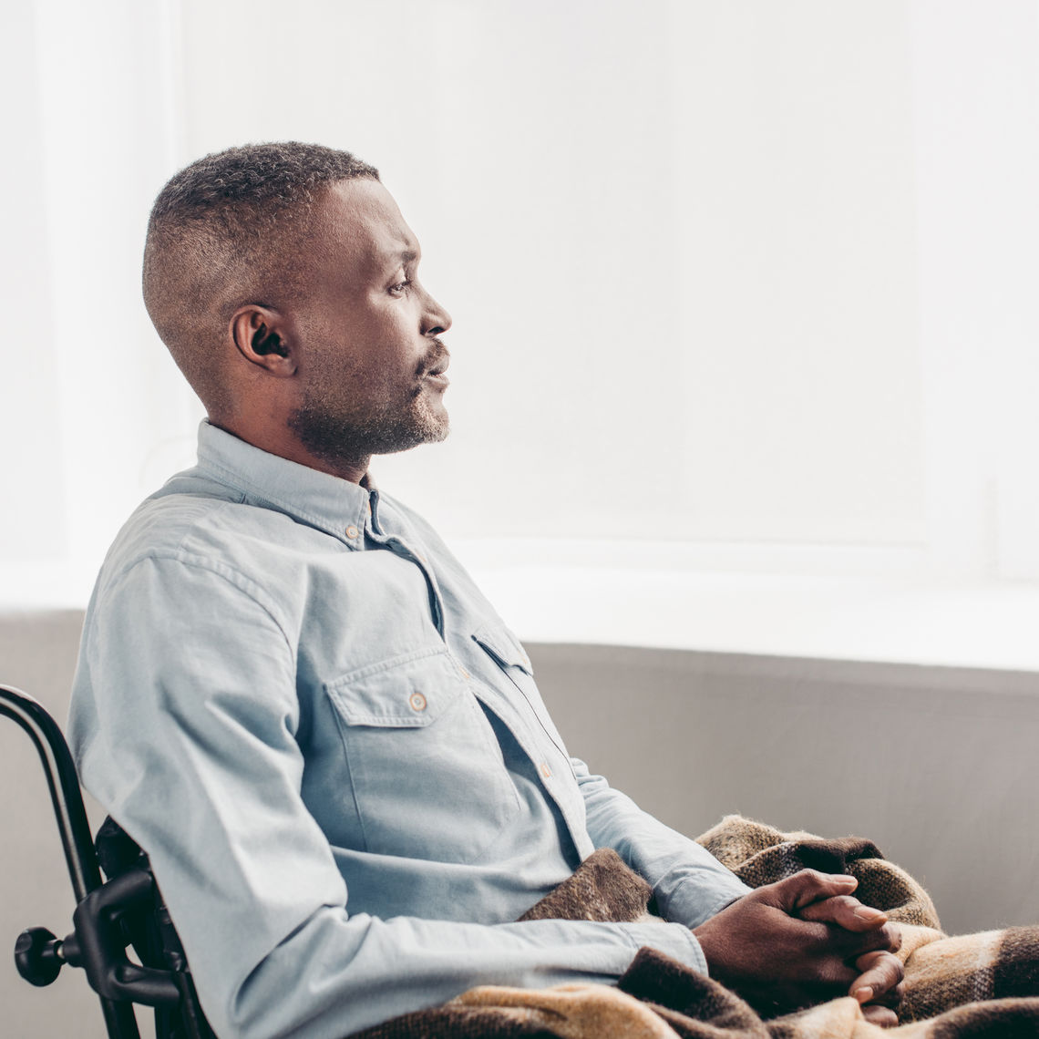 side view of man sitting in wheelchair and looking away