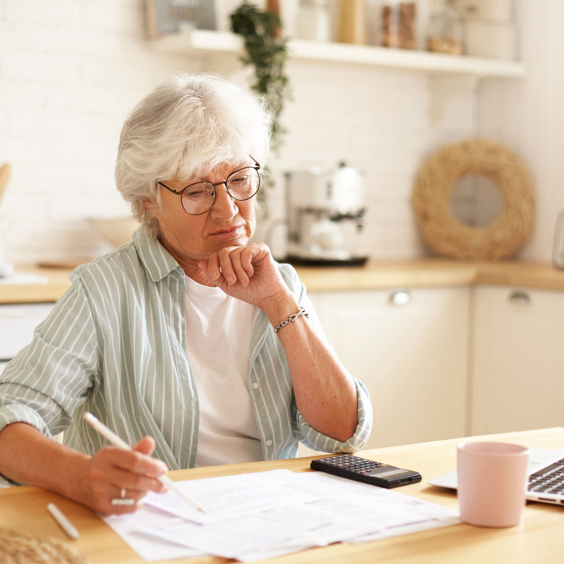 Casually dressed gray haired woman on retirement managing family budget at home, sitting in kitchen with bills, laptop, calculator and mug, writing down in papers using pencil, having focused look