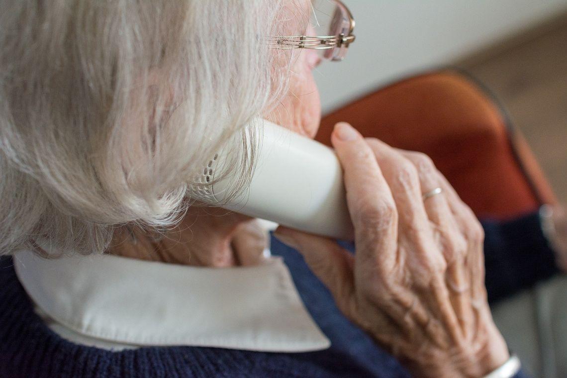 An elderly woman talks on the phone.