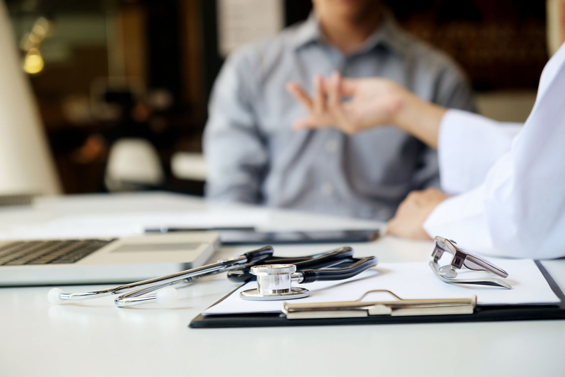 Two doctors have a discussion; they are seated at a desk with a stethoscope, laptop, and clipboard.