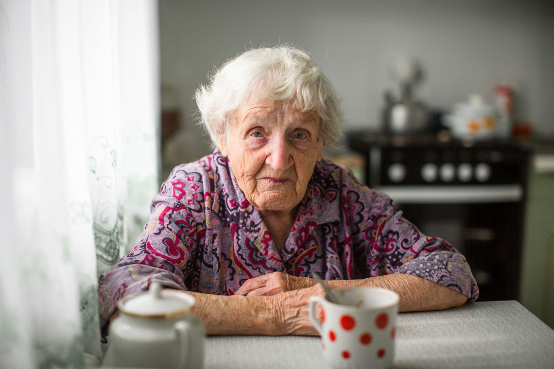 An elderly woman sitting at the kitchen table.