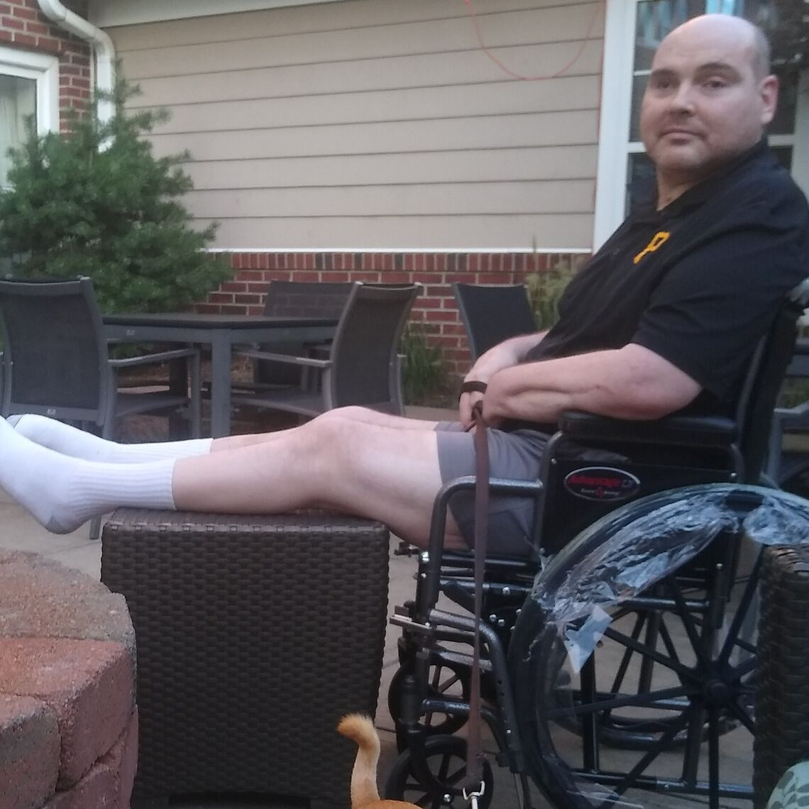 A man in a wheelchair sits on his porch with his dog