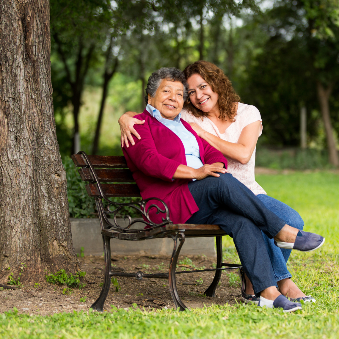A senior woman and a middle aged woman embrace on a bench under a tree.