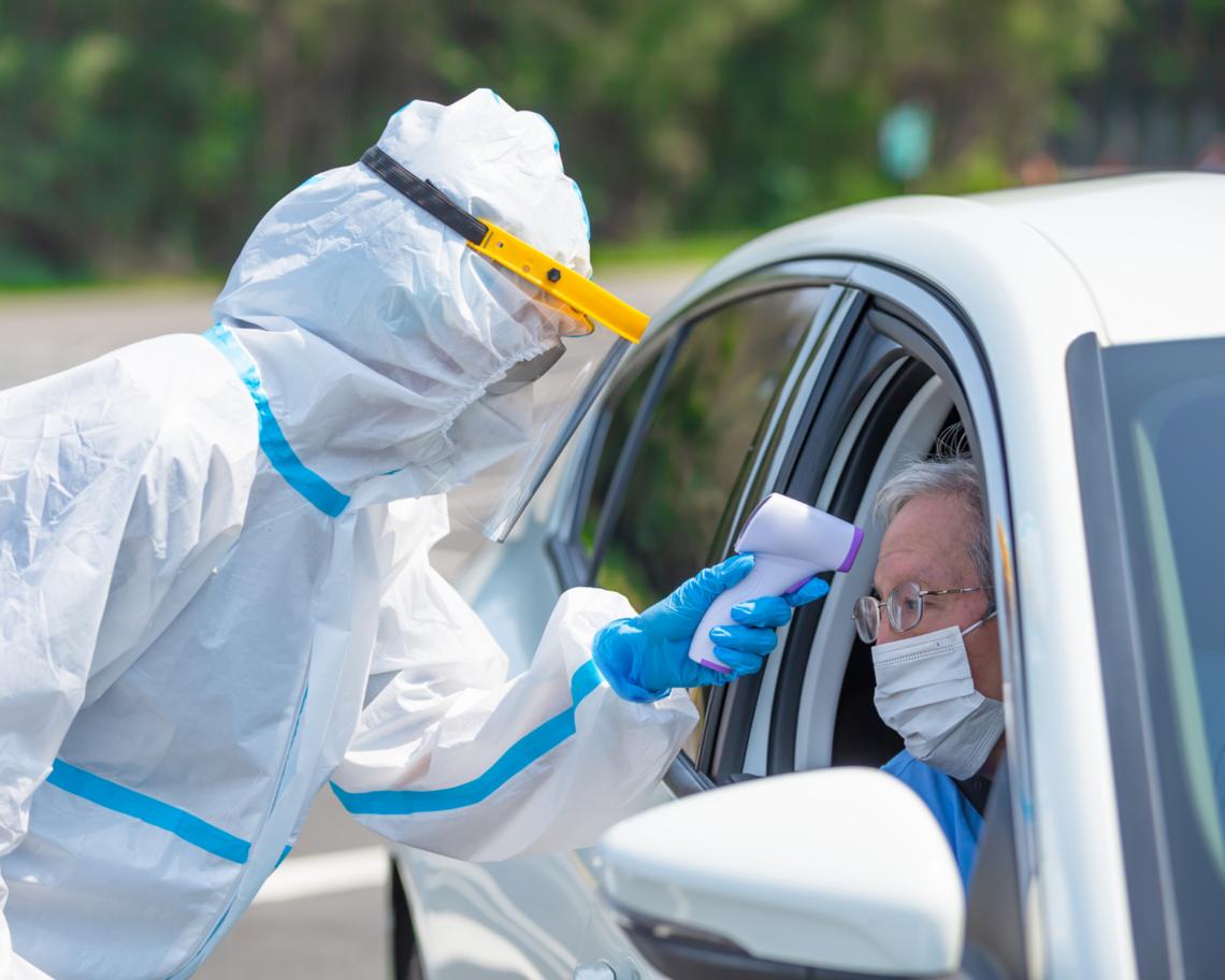 An elderly man gets a drive-through COVID test