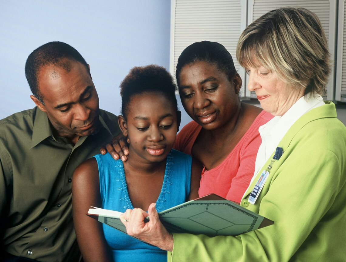 A healthcare provider discusses a chart with a girl and her parents.