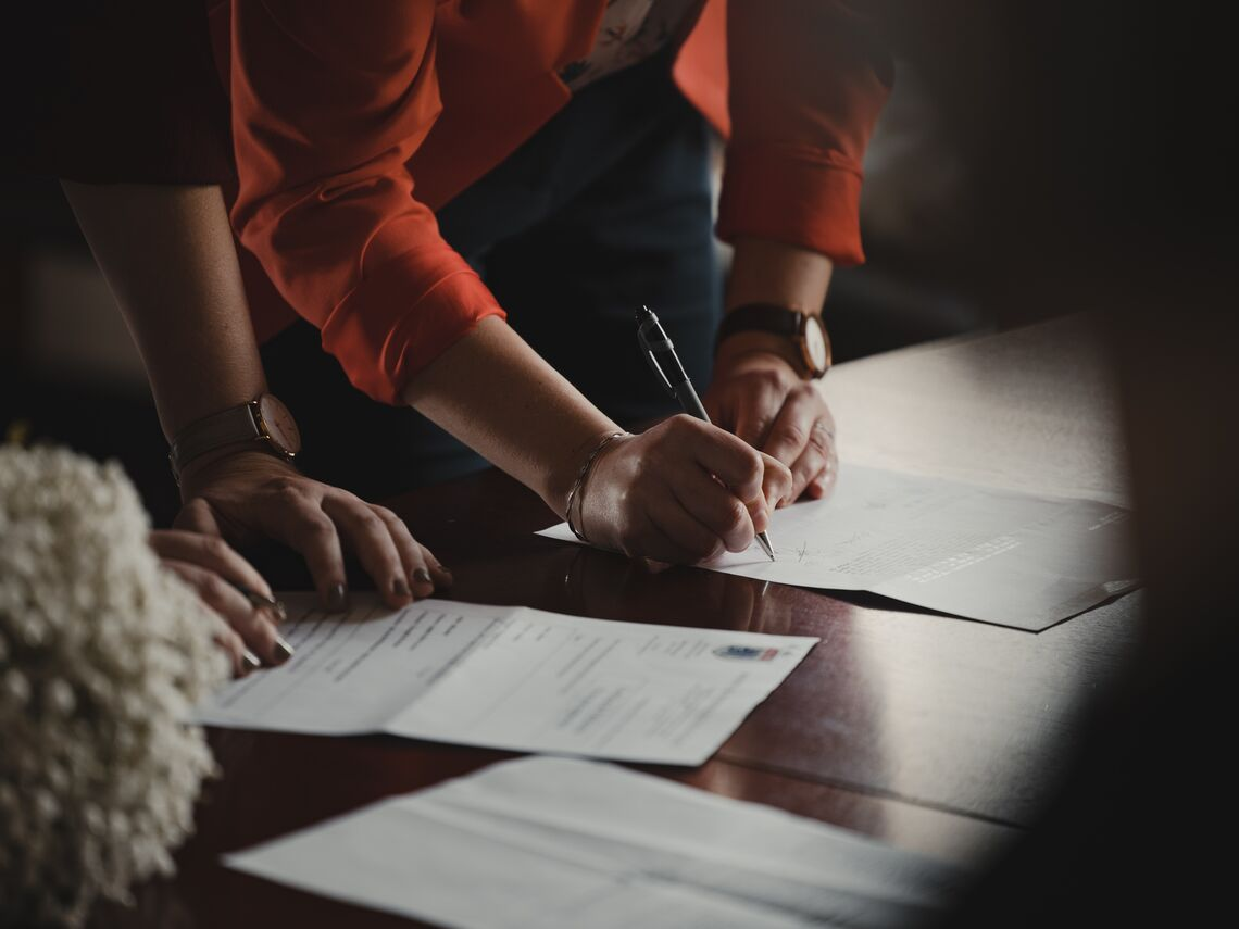 A woman signs a form on a table.