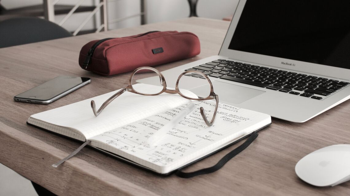 A laptop, notebook, glasses, pencil case, and phone sit on a desk.