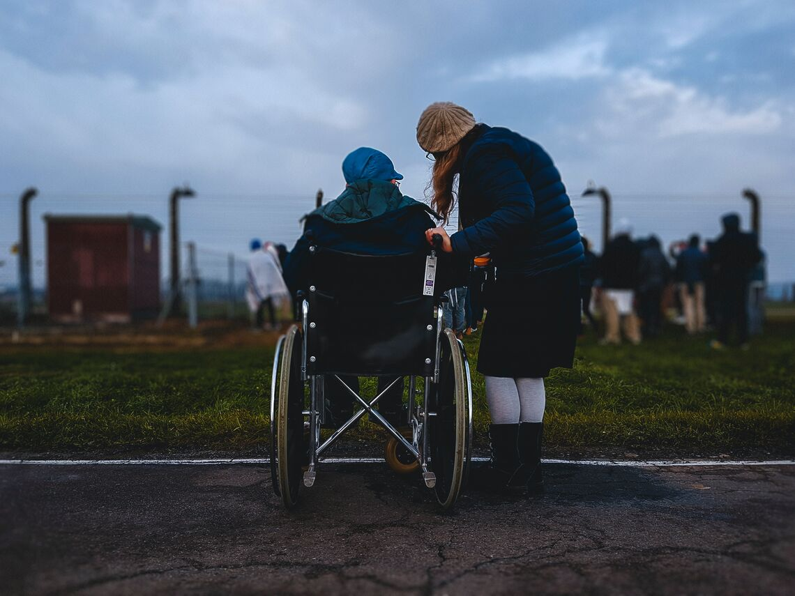 A woman stands and talks to a person in a wheelchair