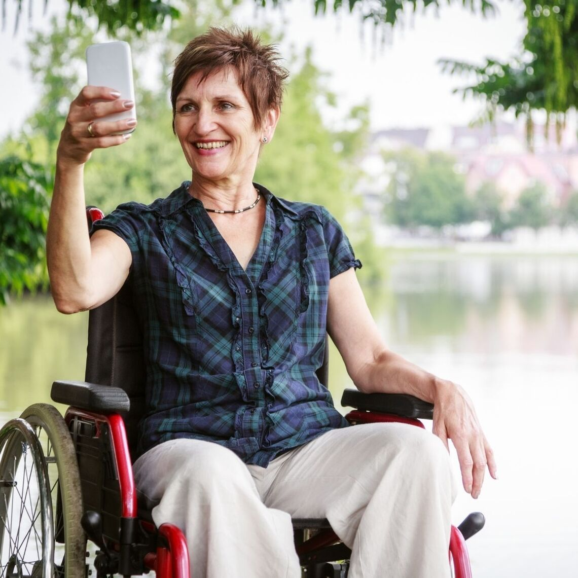 Middle aged woman in a wheelchair, taking a selfie in front of a lake
