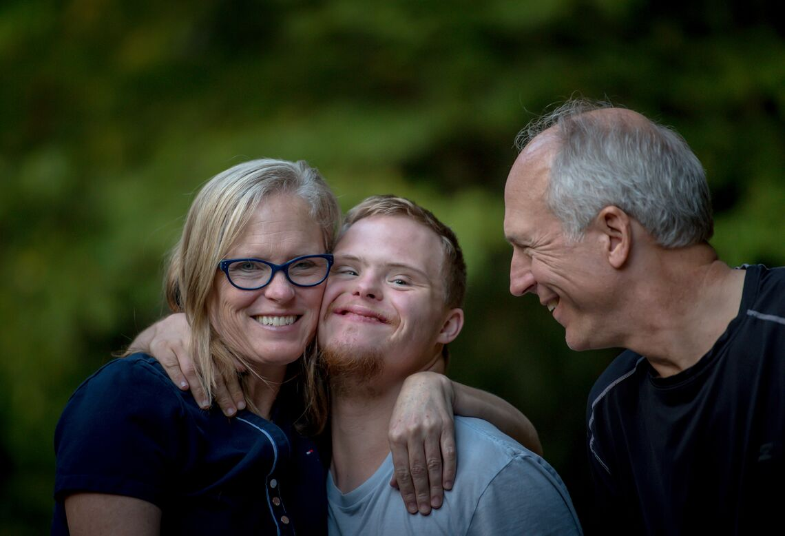 A young man with Down's syndrome and his parents smile at the camera.