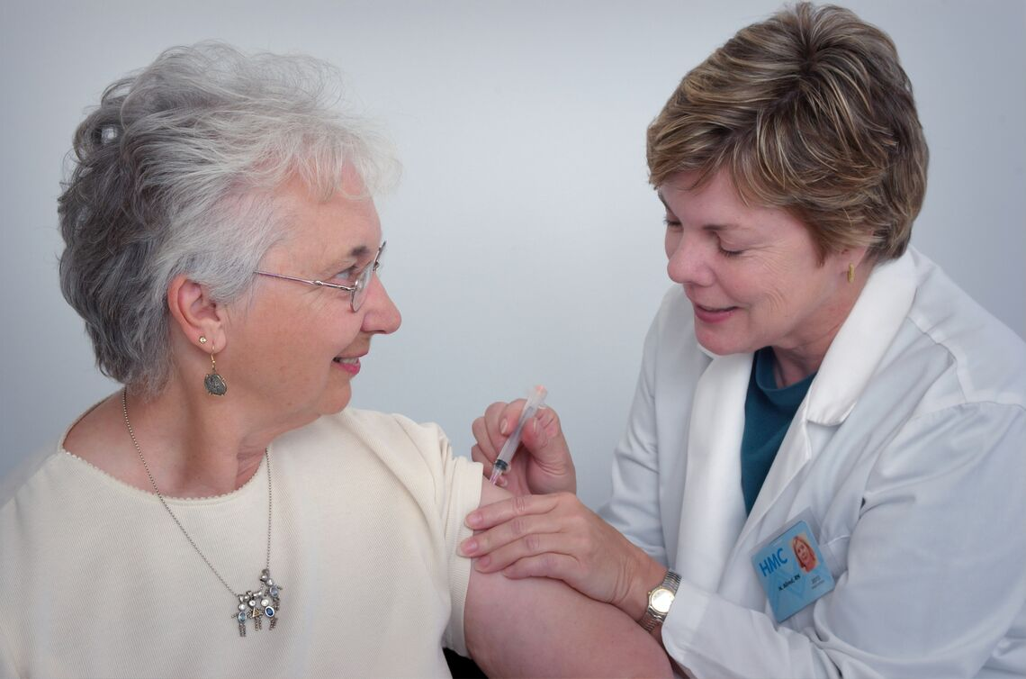 A healthcare provider gives an elderly woman a vaccine.