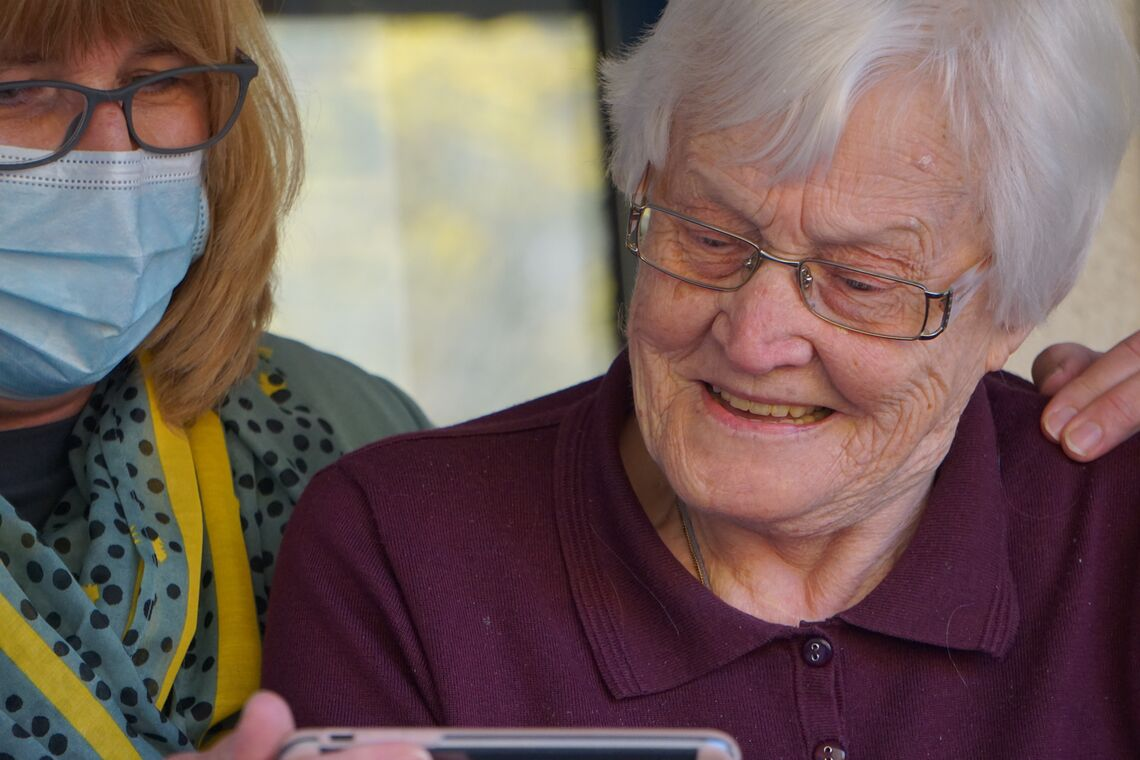 A woman shows an elderly female nursing home resident something on a phone