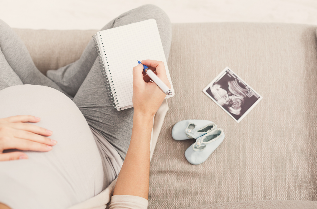 A pregnant person sits on a sofa, with one hand on their stomach and the other writing in a notebook. A pair of baby booties and an ultrasound photo are next to them on the sofa.