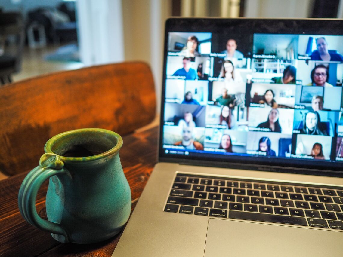 A Zoom meeting on a laptop and a teal mug